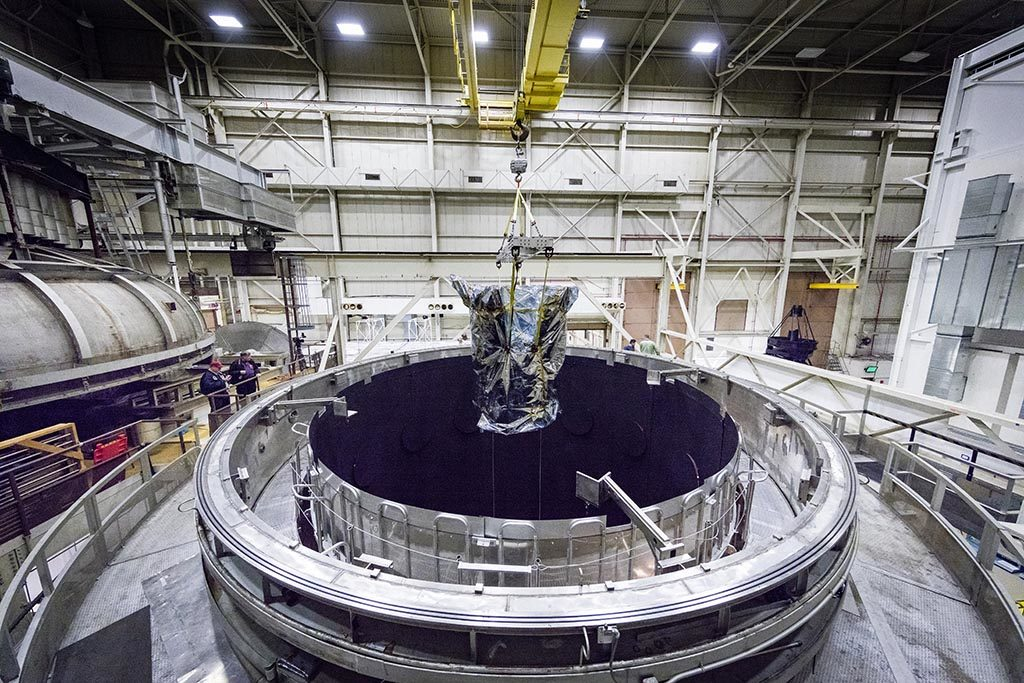 The spacecraft is seen within the opening of the thermal vacuum chamber as it is lifted out.