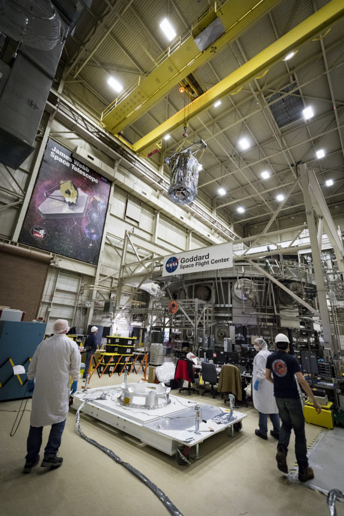 Several people watch from the ground as Parker Solar Probe is lifted by crane out of the thermal vacuum chamber.