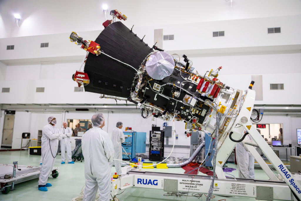 A spacecraft is held at an approximately 45 degree angle on a stand inside a clean room.
