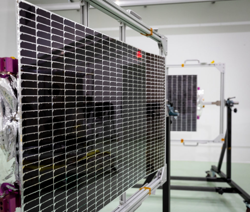 Two solar arrays it on racks in a clean room.