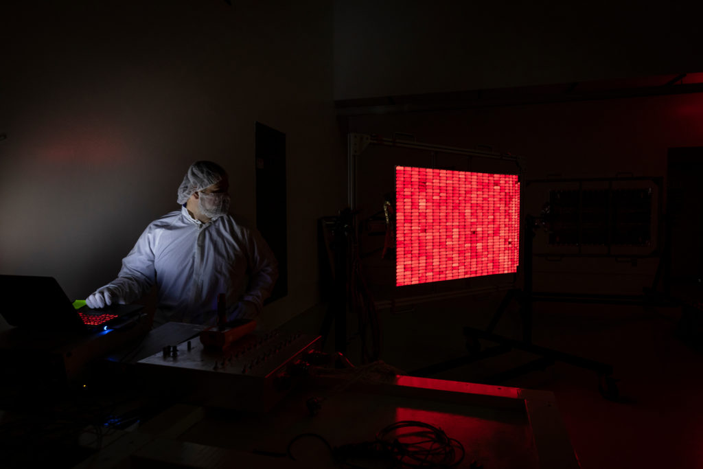 A person wearing a clean suit sits in a dark room looking a solar panel, on which all the cells are glowing red.