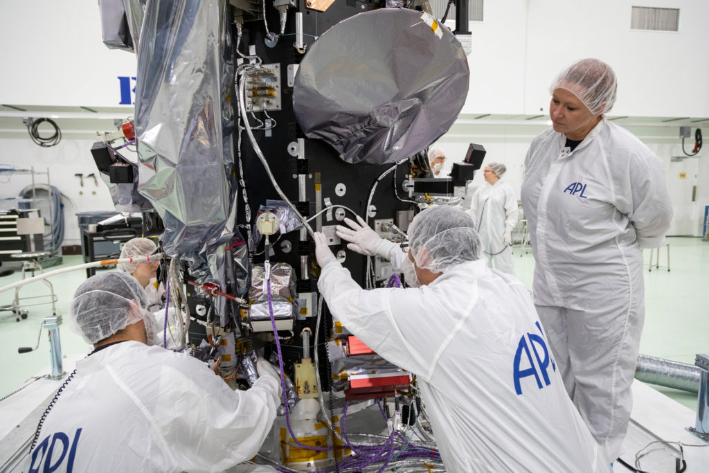 A person in a clean suit places a plaque on the side of the Parker Solar Probe spacecraft, while three other clean-suited people look on.