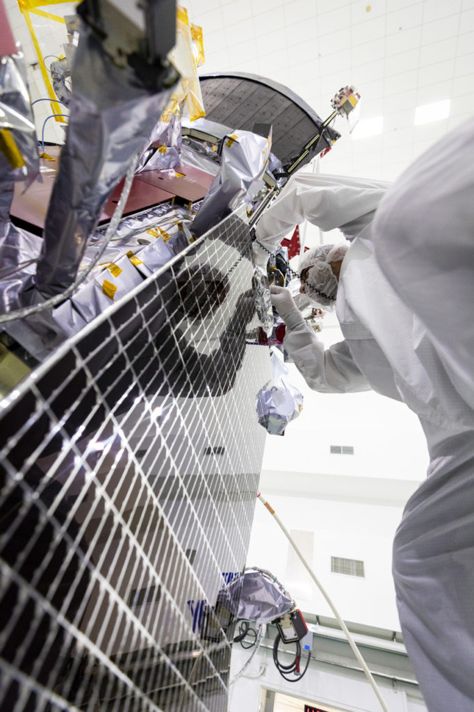 A view from the bottom of a solar panel, looking up as a person in a bunny suit works on the top of the panel.