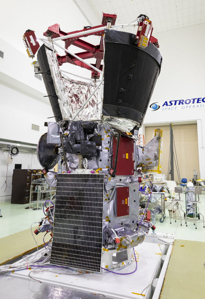A spacecraft sits in a clean room with a solar array installed on the side.