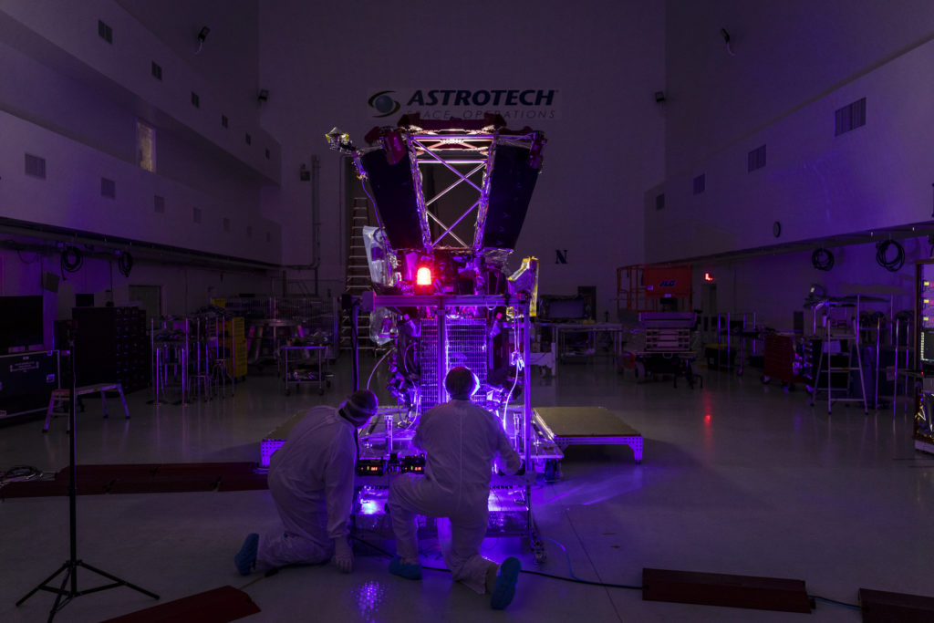 Two people in bunny suits kneel in front of a solar panel attached to a spacecraft while operating a purple laser in the dark.