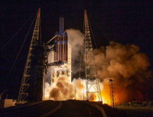 The Delta IV Heavy carrying Parker Solar Probe lifts off the pad as smoke billows beneath it.