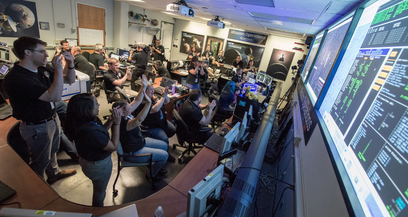 New Horizons Flight Controllers celebrate after receiving confirmation from the spacecraft that it had successfully completed the flyby of Pluto, Mission Operations Center (MOC) of the Johns Hopkins University Applied Physics Laboratory (APL), Laurel, Maryland. Credits: (NASA/Bill Ingalls)