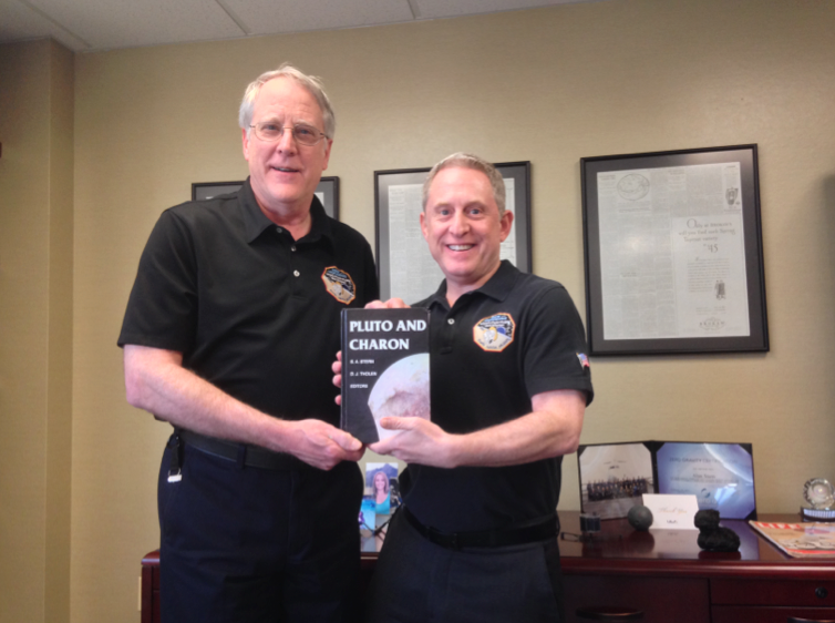 "Richard Binzel and Alan Stern with the 1997 book ""Pluto and Charon,"""