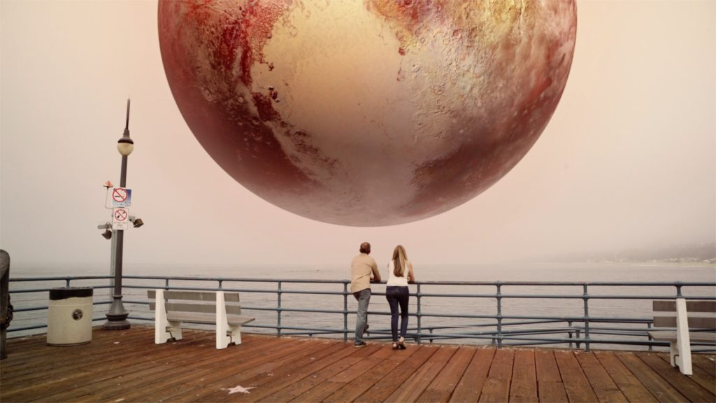 image of 2 people standing under Pluto