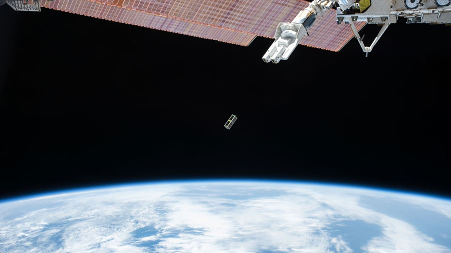 A Cubesat is ejected from a deployer mechanism on the outside of Japan's Kibo laboratory module.