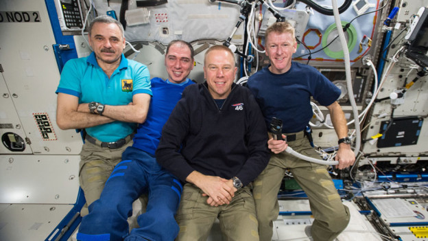 Astronauts Ready Spacesuits  as Commander Observes Moment of Silence