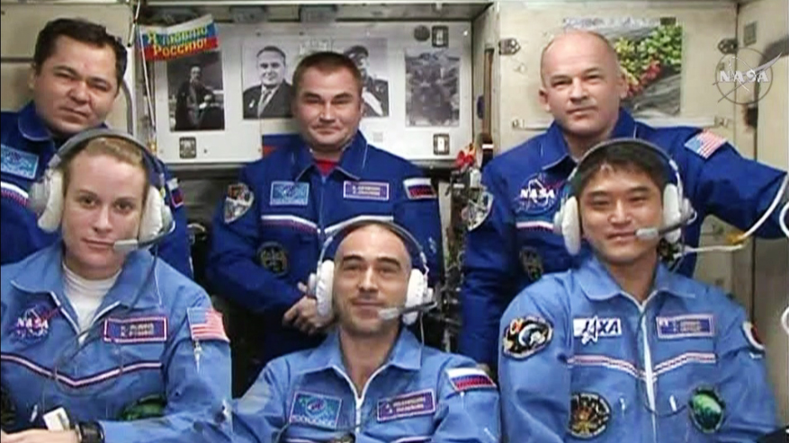 The six-member Expedition 48 crew join each other for well wishes and congratulations from family, friends and mission officials. In front, from left are the new crew members Kate Rubins, Anatoly Ivanishin and Takuya Onishi. In the back row are Flight ENgineers Oleg Skripochka and Alexey Ovchinin and Commander Jeff Williams. Credit: NASA TV