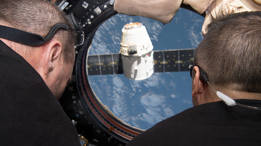 Flight Engineers Scott Tingle and Joe Acaba monitor the departure of the SpaceX Dragon