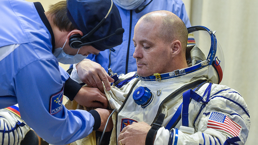 NASA astronaut Scott Tingle is helped into his Russian Sokol spacesuit