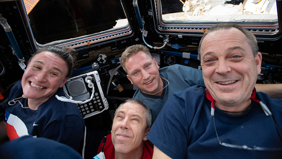Four Expedition 56 crew members gather inside the Cupola