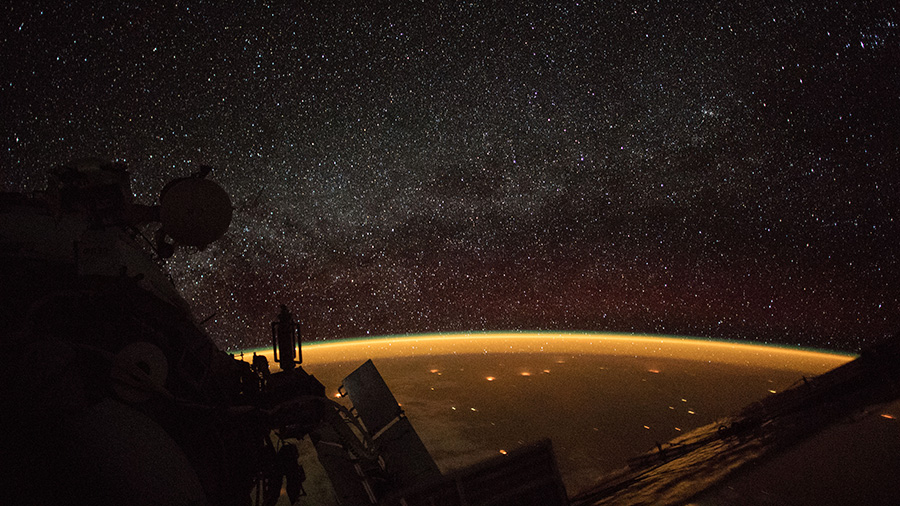 Celestial view of Earth's atmospheric glow and the Milky Way