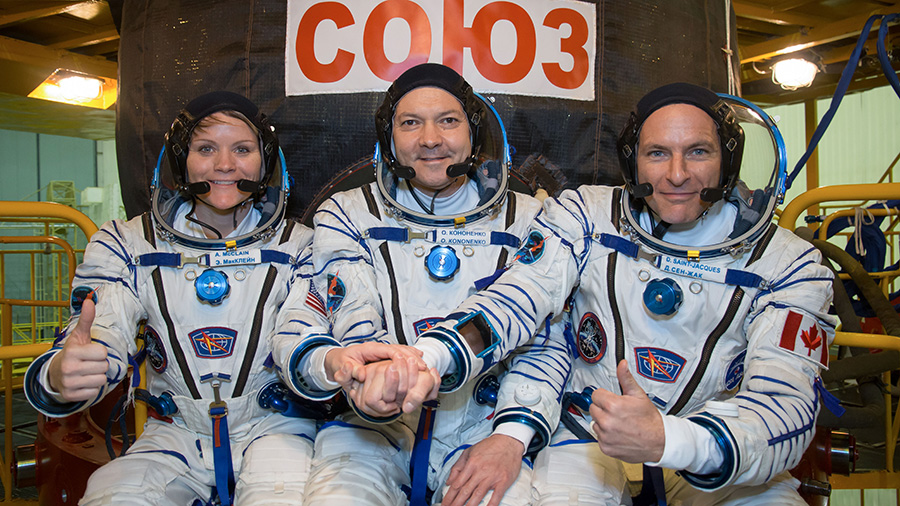 Expedition 58 crew members in front of their Soyuz MS-11 spacecraft
