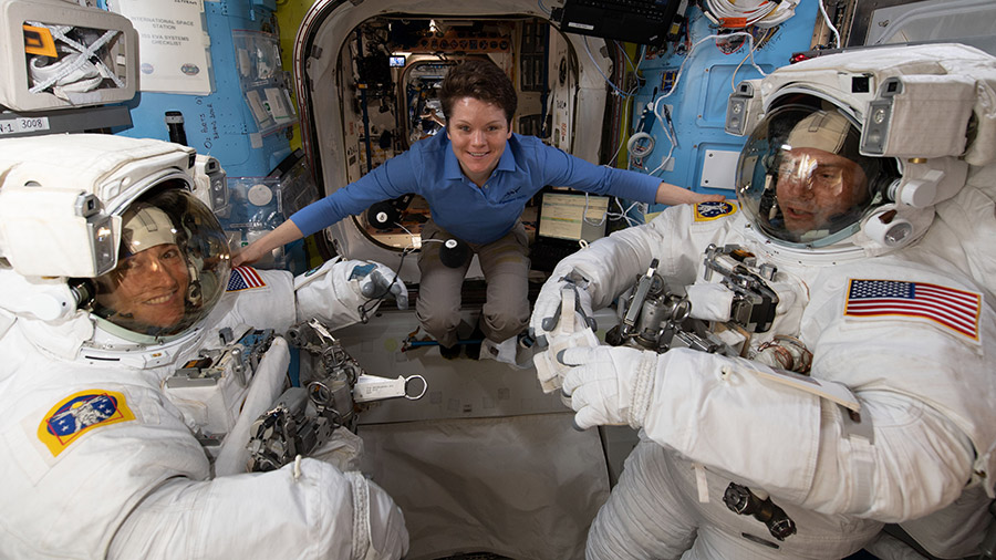 Astronaut Anne McClain assists fellow astronauts Christina Koch (left) and Nick Hague