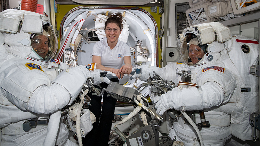 Astronaut Christina Koch assists spacewalkers Nick Hague and Anne McClain