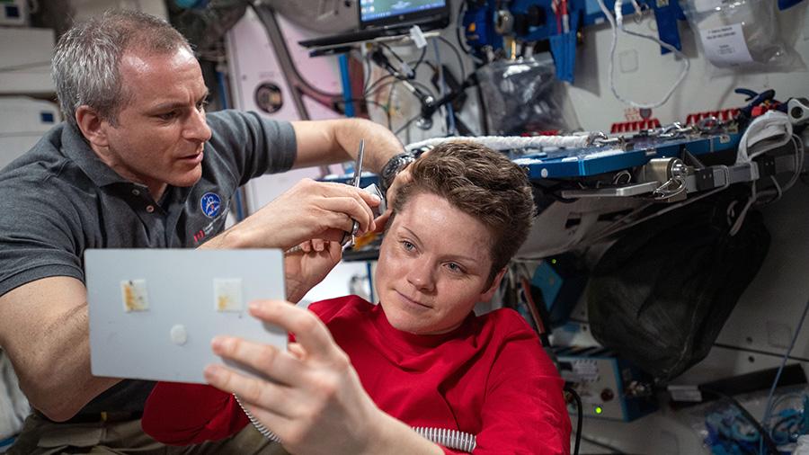 David Saint-Jacques of the Canadian Space Agency trims NASA astronaut Anne McClain's hair