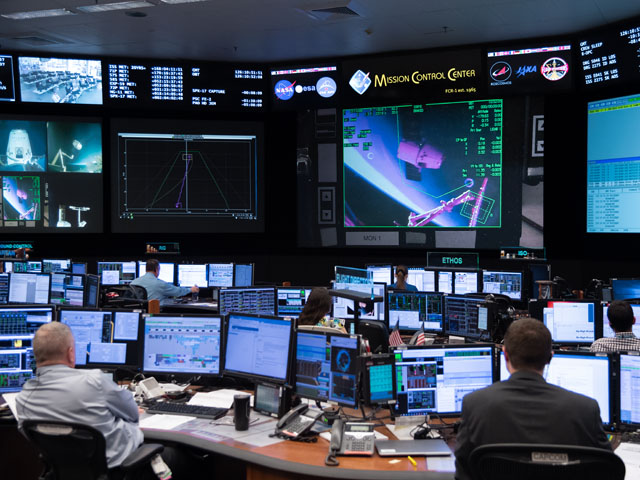 At the Mission Control Center in Houston, Expedition 59 flight controllers monitor the capture and berthing of the SpaceX Dragon cargo craft to the Harmony module of the International Space Station on May 6. Image Credit: NASA/Josh Valcarcel