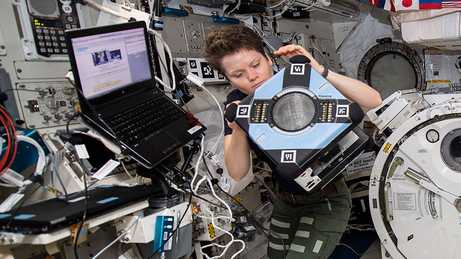 Astronaut Anne McClain checks out the new Astrobee hardware