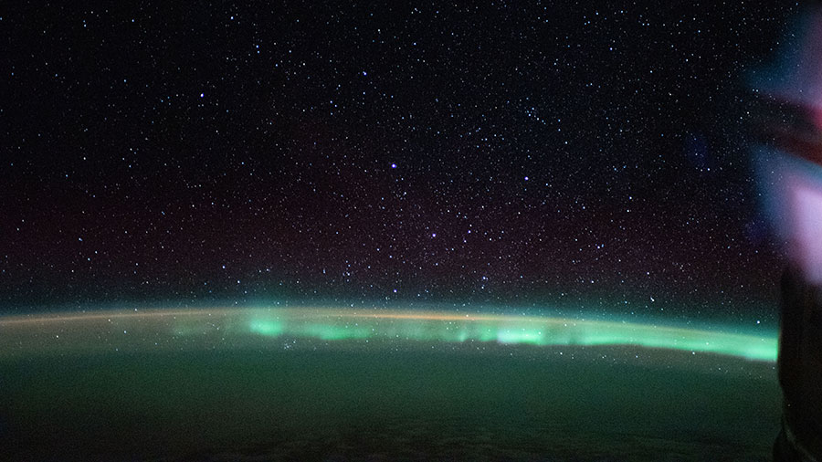 "The aurora australis, or ""southern lights,"" highlights a starry nighttime orbital pass"