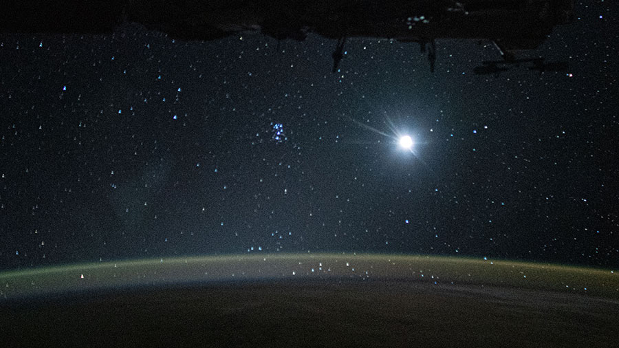 Earth's atmospheric glow, highlighted by the Moon and a starry orbital nighttime