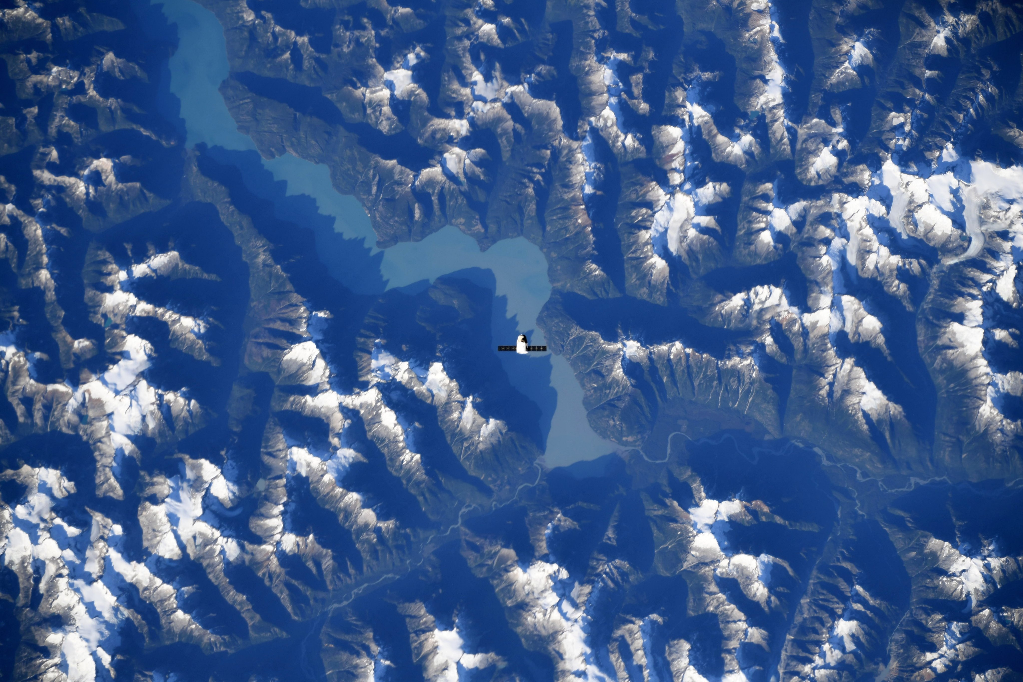 The SpaceX Dragon resupply ship is pictured above the Canadian Rocky Mountains