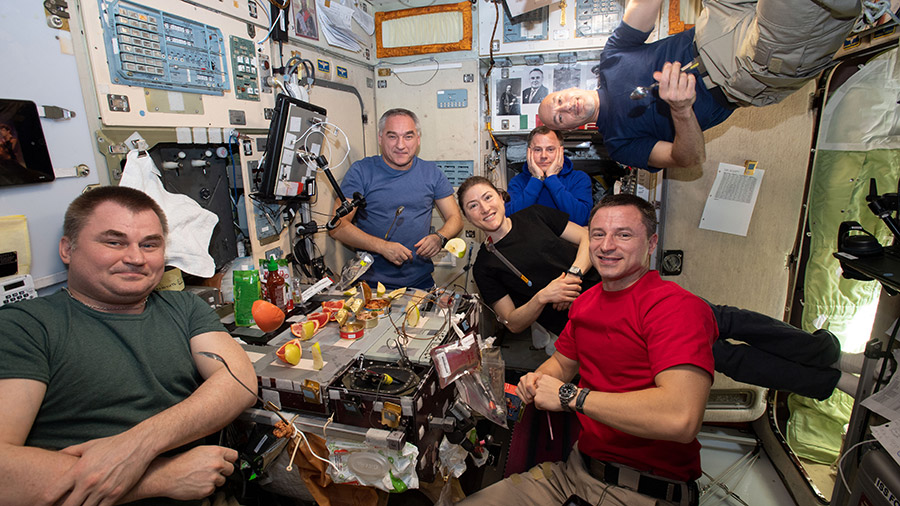 The six-member Expedition 60 crew is gathered together for dinner