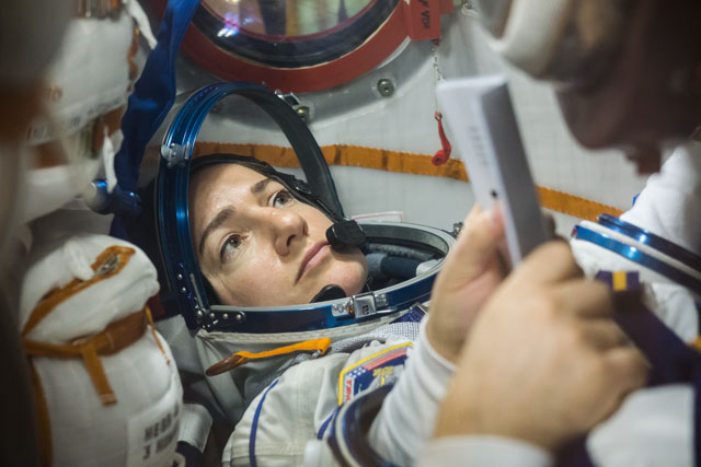 In the Integration Building at the Baikonur Cosmodrome in Kazakhstan, Expedition 61 crew member Jessica Meir of NASA runs through procedures Sept. 11 aboard the Soyuz MS-15 spacecraft during an initial Soyuz vehicle fit check. Credit: NASA/Victor Zelentsov