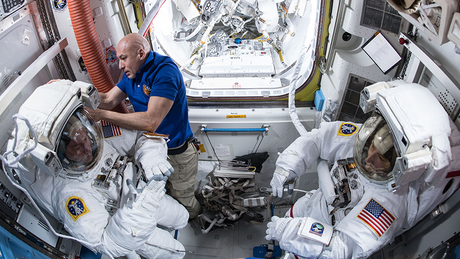 Expedition 61 Commander Luca Parmitano assists astronauts Andrew Morgan and Christina Koch in their U.S. spacesuits