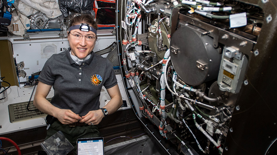 Astronaut Christina Koch works on orbital plumbing tasks