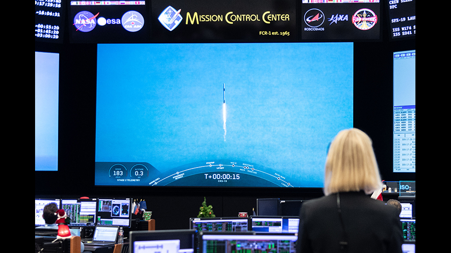 A mission controller in Houston watches the SpaceX Dragon resupply ship blast off