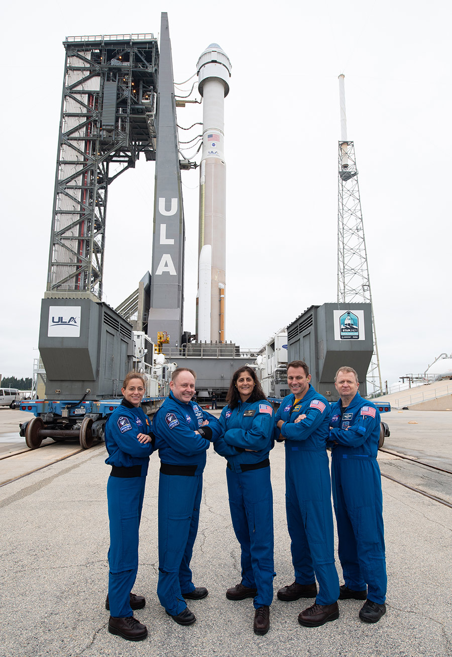 NASA astronauts pose with Boeing's CST-100 Starliner spacecraft behind them