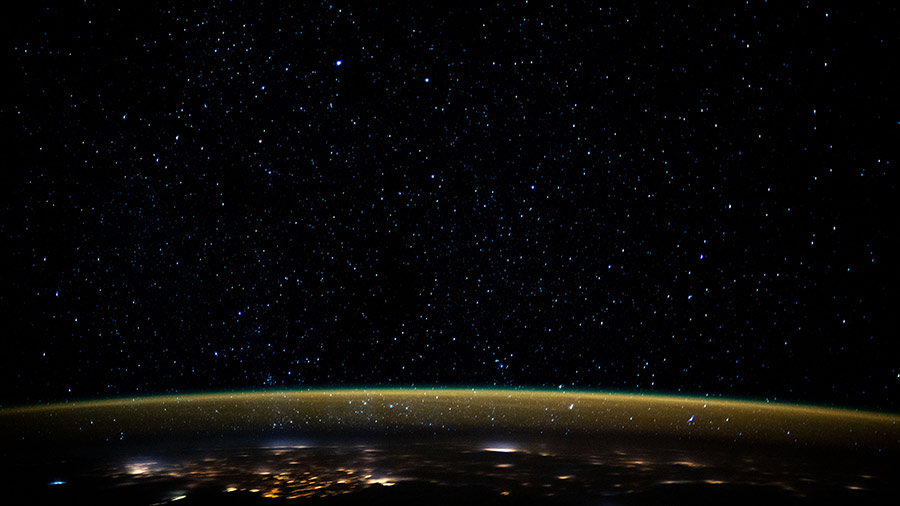 Stars glitter in the night sky above an atmospheric glow