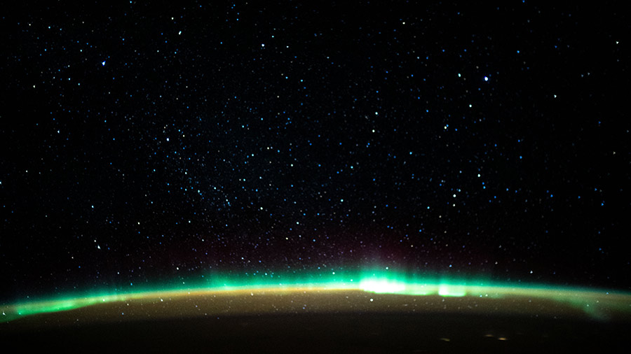 An aurora blankets the Earth beneath a celestial night sky