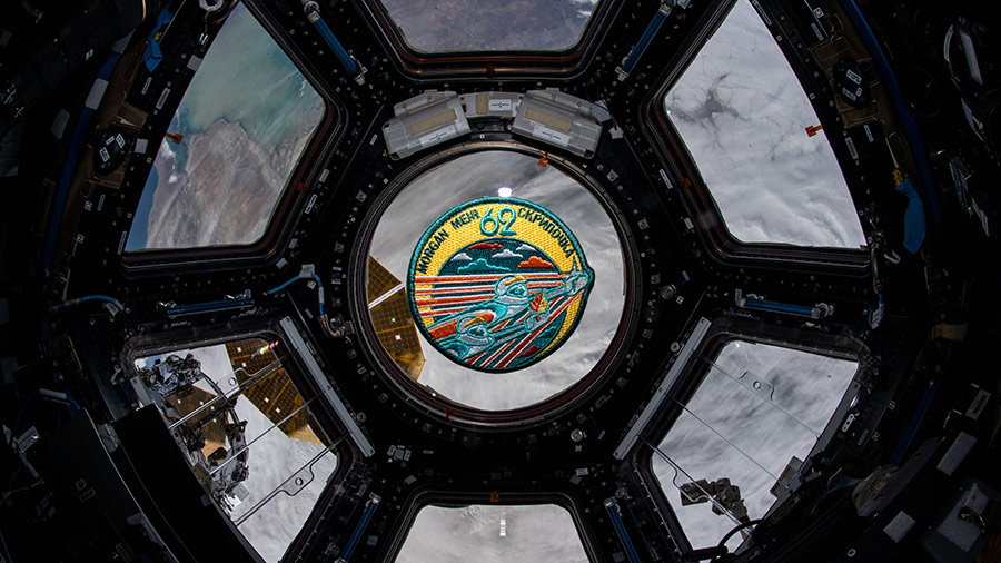 The Expedition 62 mission patch floats inside the seven-window cupola