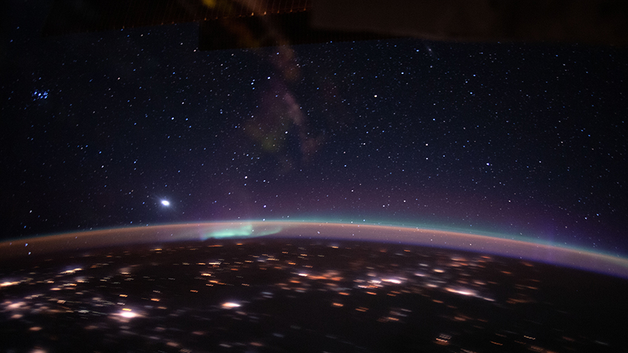 An aurora accents Earth's atmospheric glow