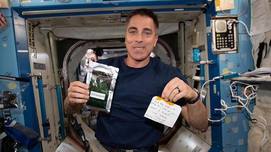 NASA astronaut Chris Cassidy holds a Parmigiana di Melanzane meal packet