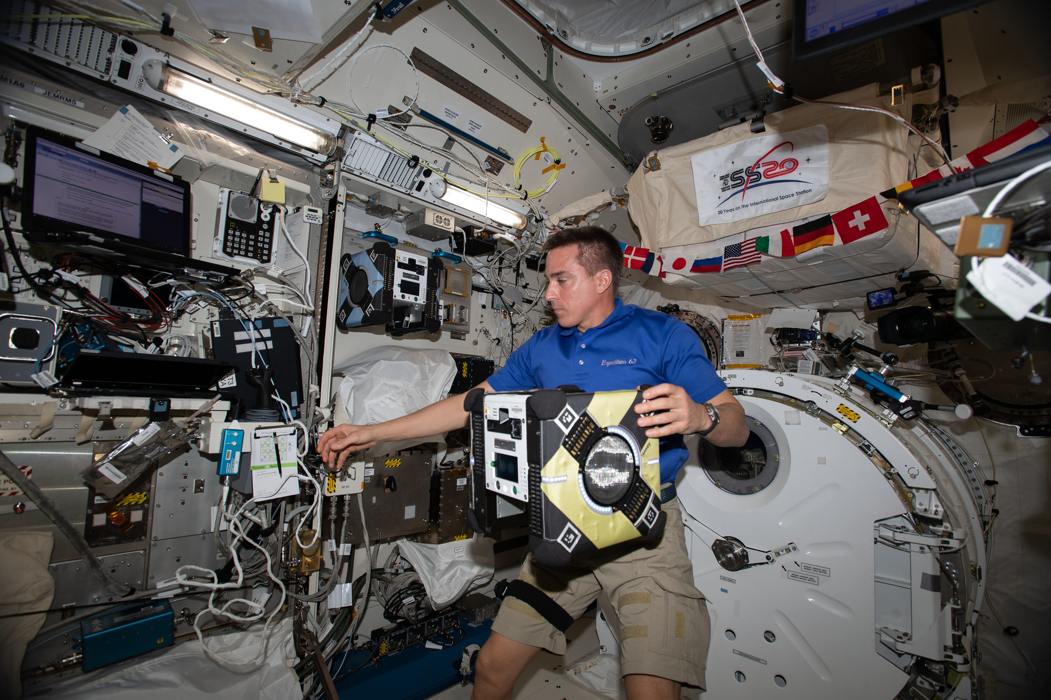 NASA astronaut and Expedition 63 Commander Chris Cassidy sets up an Astrobee robotic assistant
