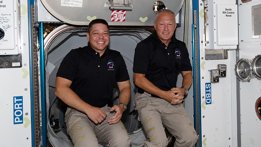 The International Space Station's two newest crew members, NASA astronauts (from left) Bob Behnken and Doug Hurley, are pictured having just entered the orbiting lab shortly after arriving aboard the SpaceX Crew Dragon spacecraft. Credits: NASA