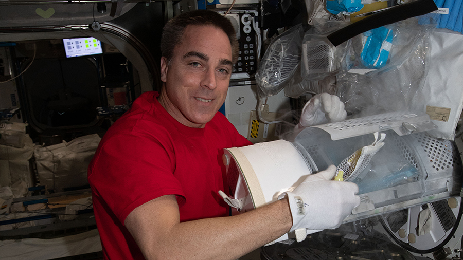 Expedition 63 Commander Chris Cassidy prepares to stow biological samples for preservation inside a science freezer.