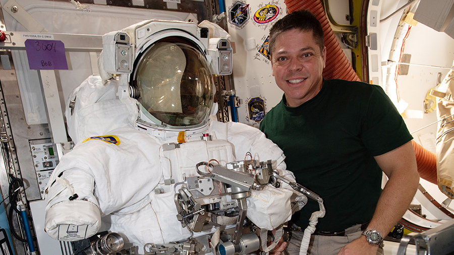 Expedition 63 Flight Engineer Bob Behnken poses with a U.S. spacesuit