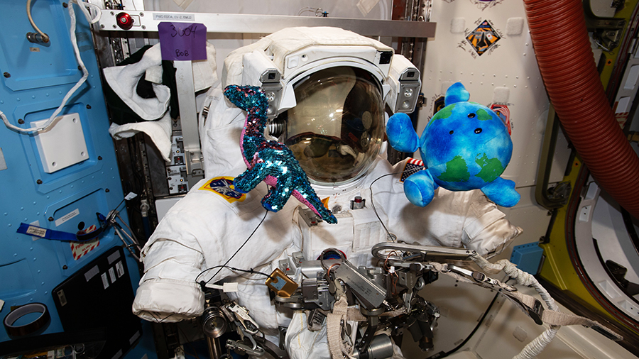 A U.S. spacesuit is pictured surrounded by a pair of plush-doll mascots