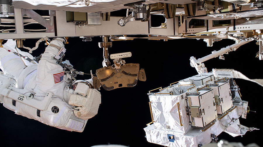 NASA astronaut Bob Behnken (at left) is pictured during a spacewalk to swap batteries on June 26.