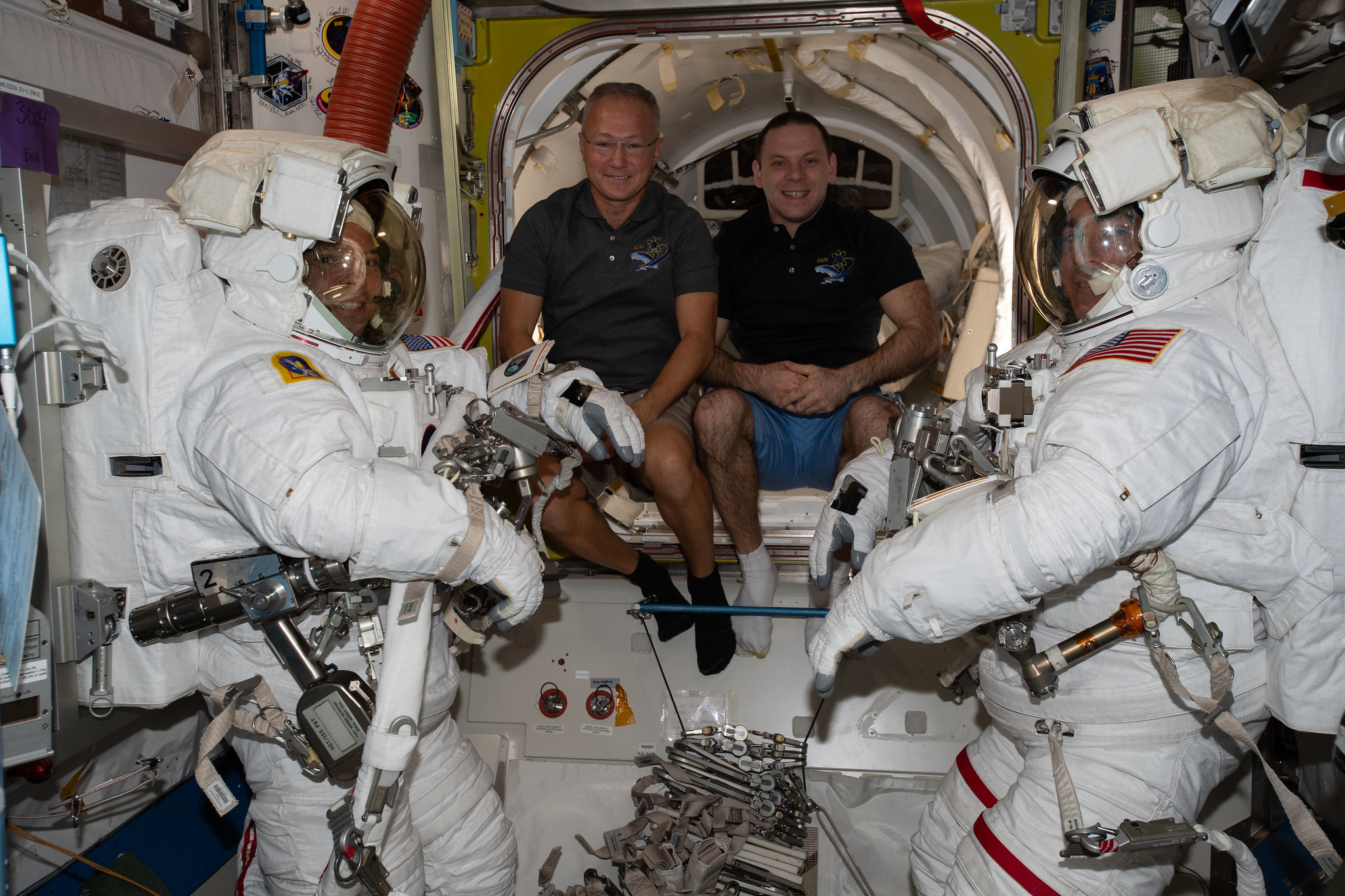Spacewalkers Bob Behnken (far left) and Chris Cassidy (far right) are suited up ahead of their June 26 spacewalk.
