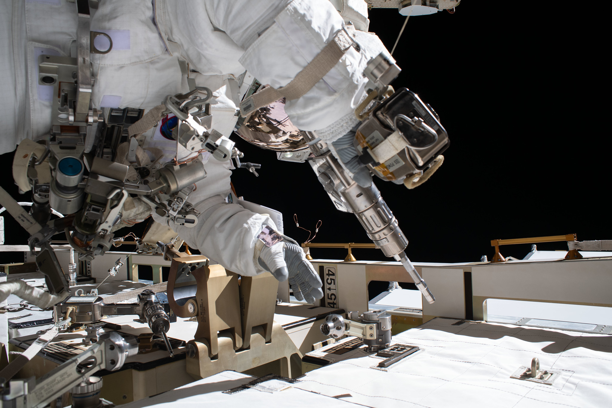 NASA astronaut and Expedition 63 Flight Engineer Bob Behnken works during a spacewalk to swap an aging nickel-hydrogen battery for a new lithium-ion battery on the International Space Station's Starboard-6 truss structure.