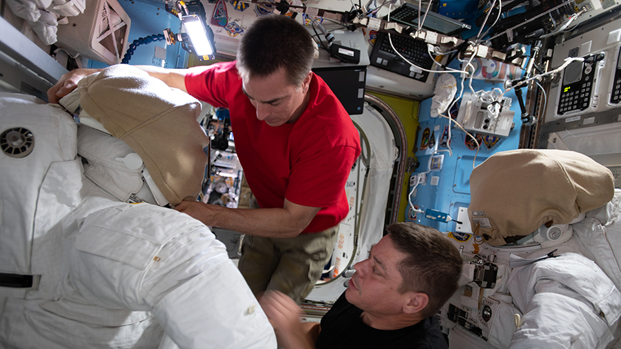 NASA astronauts (from top) Chris Cassidy and Bob Behnken work on U.S. spacesuits inside the International Space Station's Quest airlock.
