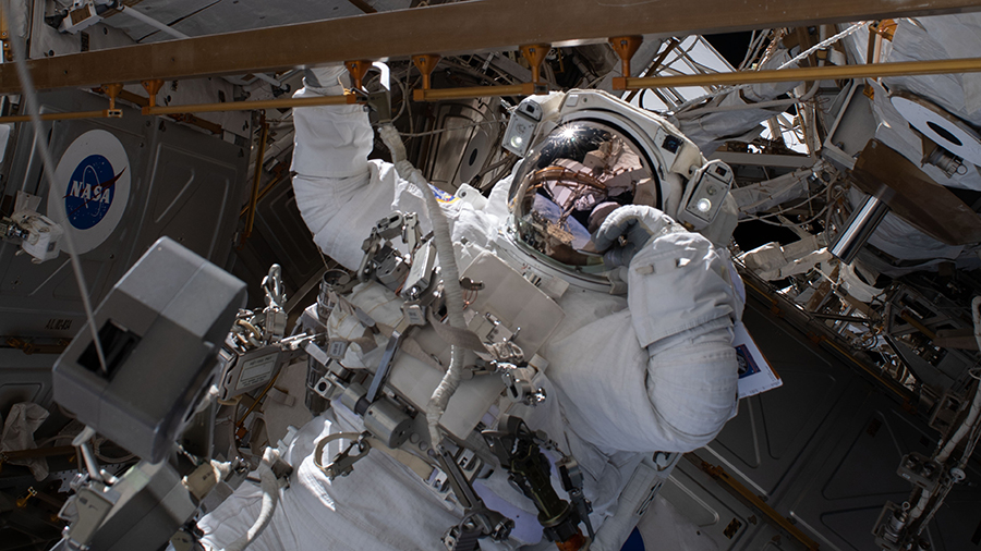 Astronaut Bob Behnken works during a spacewalk to swap an aging nickel-hydrogen battery for a new lithium-ion battery.